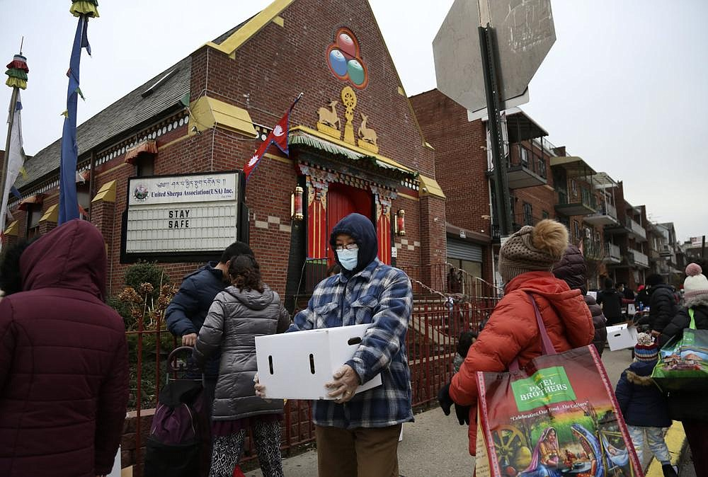People receive free food from the United Sherpa Association's weekly food pantry in the Queens  borough of New York. The pantry began in April with a focus on the Nepalese community, international students and families living in the country without permission.