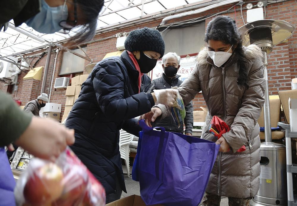 United Sherpa Association  treasurer Tshering  Sherpa  (center)  helps college students Jyoti Rajbanshi of Long Island University  (left) and Lalsa Pandit of Laguardia Community College  (right)  pack free food in bags during the group's weekly food pantry in  the Queens borough of New York.