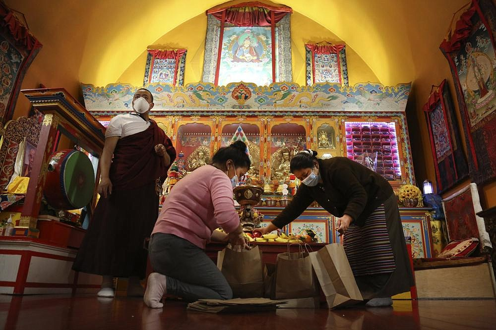 Lama Gelbu (left), Pasang Sherpa (center) and Yanddu Lama (right) prepare bags of fruit used as  ceremonial offerings at the conclusion of the Dakini Day practice, a group meditation that includes  song and food and is celebrated on the 25th day of each lunar month, at the United Sherpa Association in the Queens borough of New York.