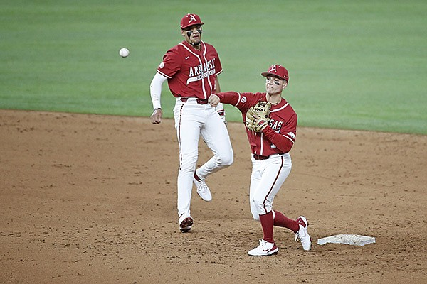 Arkansas second baseman Robert Moore throws during warmups as shortstop Jalen Battles looks on prior to a game against Texas Tech on Saturday, Feb. 20, 2021, in Arlington, Texas.