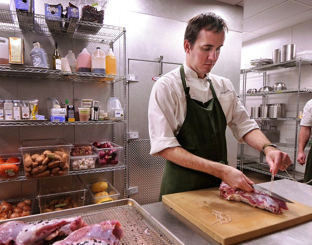 FILE PHOTO -- In this November 22, 2013, file photo, Executive Chef Matthew McClure prepares a leg of goat roast in the kitchen at The Hive restaurant in 21c Museum Hotel in Bentonville. (Ben Goff/NWA Democrat-Gazette)