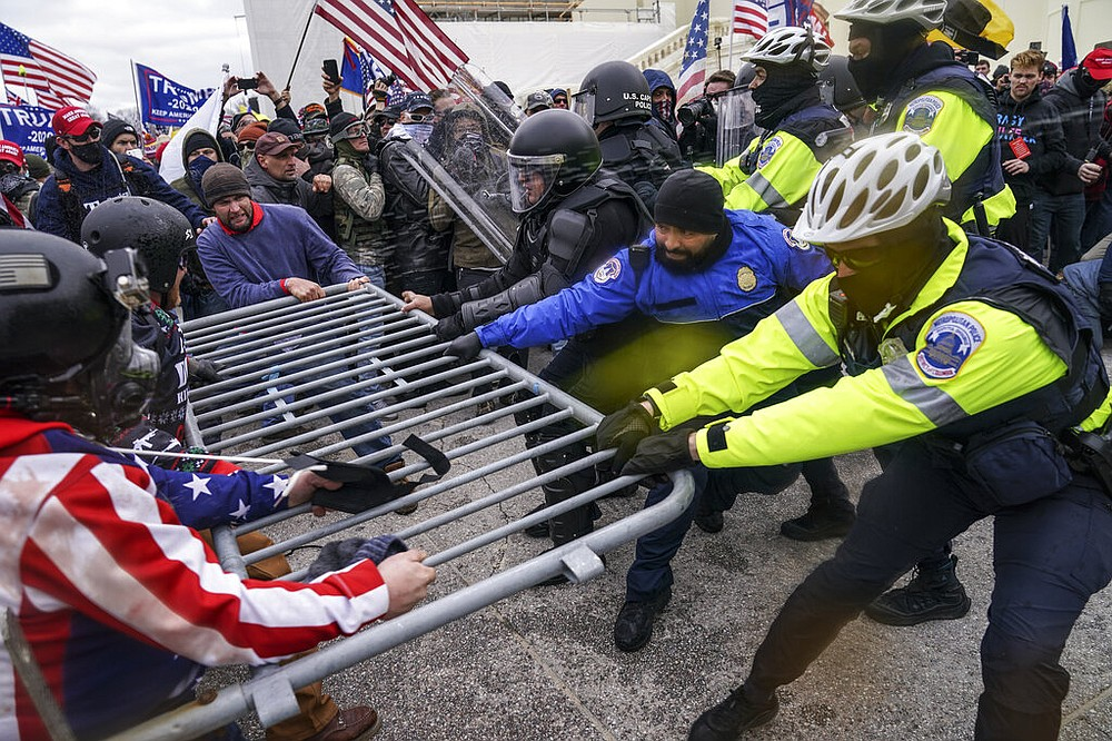 FILE - In this Jan. 6, 2021, file photo rioters try to break through a police barrier at the Capitol in Washington. Congress is set to hear from former security officials about what went wrong at the U.S. Capitol on Jan. 6.