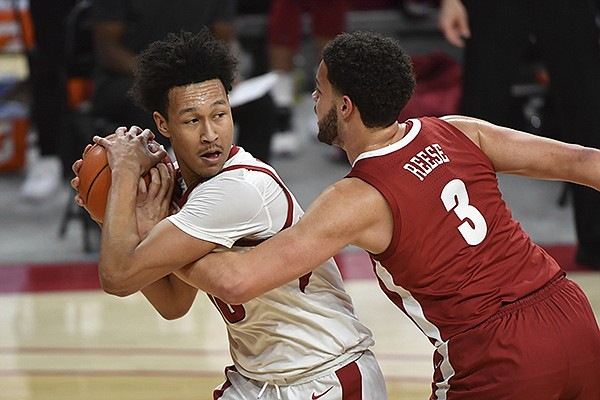 Arkansas forward Jaylin Williams tries to keep the ball from Alabama forward Alex Reese (3) during the second half of an NCAA college basketball game in Fayetteville, Wednesday, Feb. 24, 2021. (AP Photo/Michael Woods)