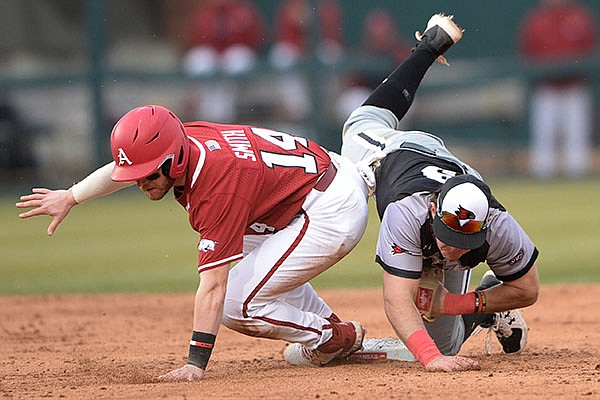 Caption: Arkansas third baseman Cullen Smith (14) collides Thursday, Feb. 25, 2021, with Southeast Missouri State shortstop Tyler Wilber at Baum-Walker Stadium in Fayetteville.