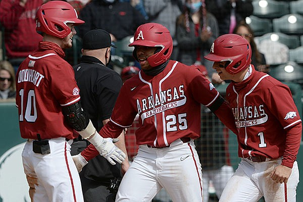 Arkansas center fielder Christian Franklin (25) is congratulated at the plate Saturday, Feb. 27, 2021, by second baseman Robert Moore (1) and designated hitter Matt Goodheart after Franklin hit a two-run home run to score Moore during the second inning of the Razorbacks' 9-3 win over Southeastern Missouri State at Baum-Walker Stadium in Fayetteville.