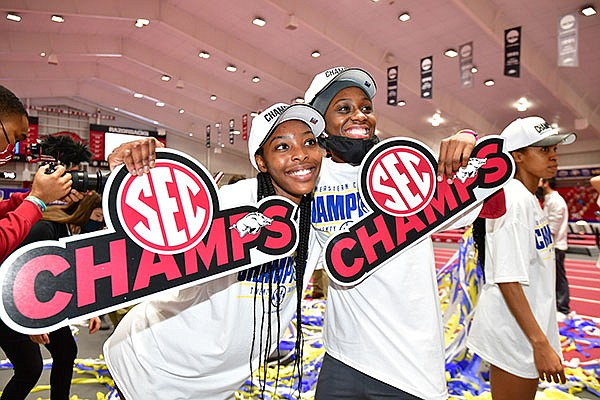 Arkansas runners Rosey Effiong (left) and G'Auna Edwards celebrate after the Razorbacks won the team title at the SEC Indoor Championships on Saturday, Feb. 27, 2021, in Fayetteville.
