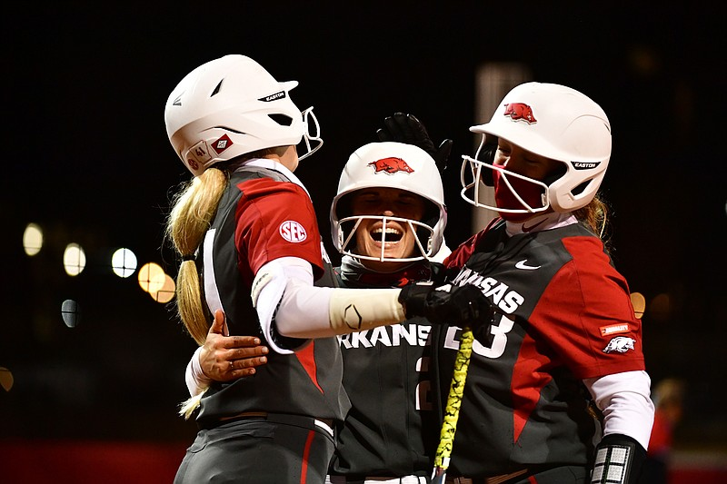 Arkansas' Braxton Burnside (center) is congratulated after hitting a home run during a game against Southeast Missouri State on Saturday, Feb. 27, 2021, in Fayetteville.
