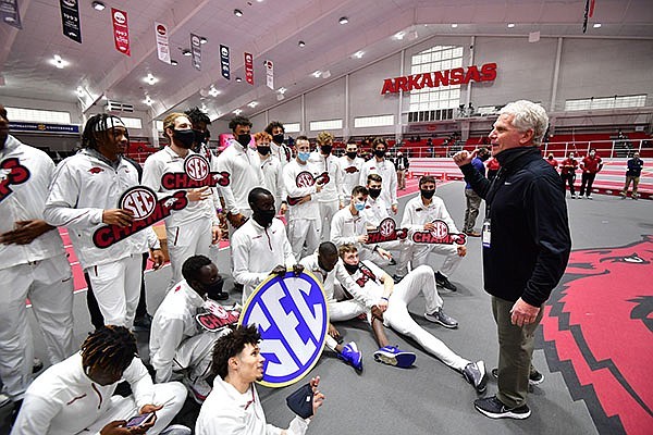 Arkansas coach Chris Bucknam (right) speaks to his team after the Razorbacks won the title at the SEC Indoor Championships on Saturday, Feb. 27, 2021, in Fayetteville.