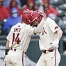 Arkansas' Cullen Smith (14) and Brady Slavens embrace after Slavens hit a home run during a game against Southeast Missouri State on Sunday, Feb. 28, 2021, in Fayetteville.
