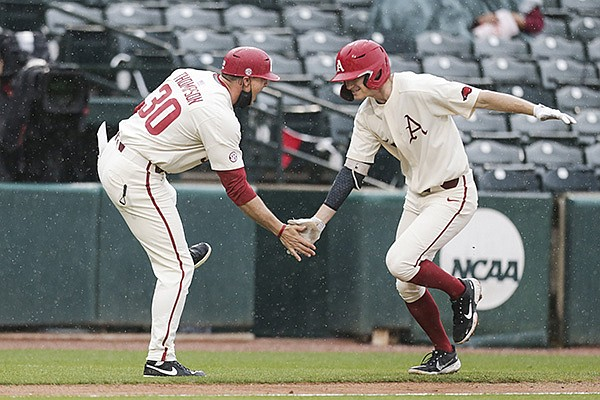 Arkansas first baseman Brady Slavens (right) celebrates with assistant coach Nate Thompson after Slavens hit a home run during a game against Southeast Missouri State on Sunday, Feb. 28, 2021, in Fayetteville.