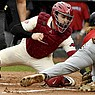 Arkansas catcher Casey Opitz (12) tags out Southeast Missouri St baserunner Ty Stauss (8) out at home during an NCAA baseball game on Sunday, Feb. 28, 2021, in Fayetteville. (AP Photo/Michael Woods)