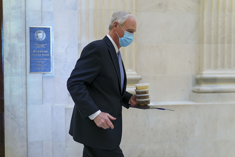 "Sen. Ron Johnson, R-Wis., leaves a Senate Republican policy luncheon Thursday. Johnson insisted that the entire text of the $1.9 trillion coronavirus relief bill be read aloud in what he said was a bid to ""shine the light on this abusive and obscene amount of money."" Senate Majority Leader Charles Schumer said he welcomed the move so the public could hear the full contents.