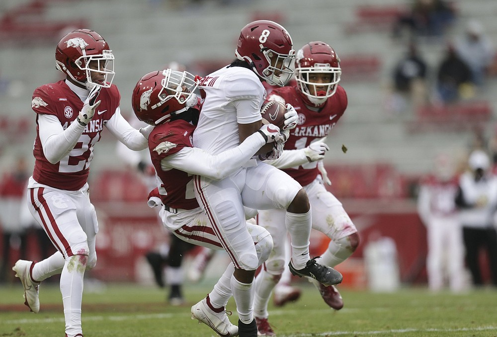 LaDarrius Bishop (24), here tackling Alabama wide receiver John Metchie in last year's game, showed his skills as a cover talent late in the season and could be among the starters in the backfield. (NWA Democrat-Gazette/Charlie Kaijo)