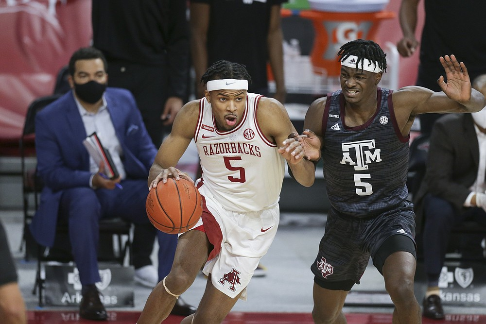 Arkansas guard Moses Moody (5) drives the ball as Texas A&M forward Emanuel Miller defends during the first half Saturday at Walton Arena in Fayetteville. Moody scored 28 points to lead the Razorbacks to an 87-80 victory. More photos at arkansasonline.com/37tamua/