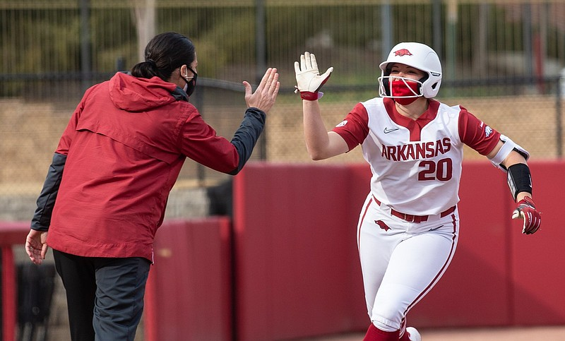 Arkansas left fielder Hannah Gammill (right) is congratulated by Coach Courtney Deifel after a home run during a recent game. Gammill is among a handful of players who are out for the Razorbacks as they begin a three-game set with South Carolina today. (Special to NWA Democrat-Gazette/David Beach)
