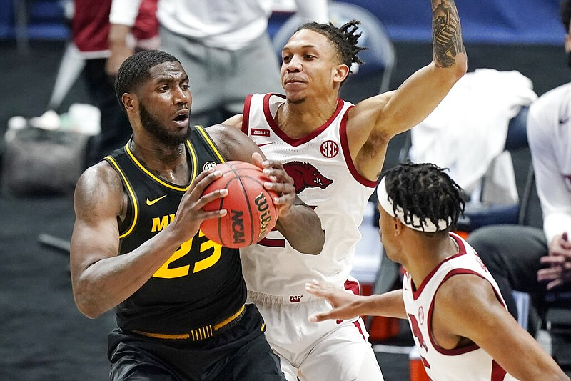 Missouri's Jeremiah Tilmon (23) is defended by Arkansas' Ethan Henderson (center) and Moses Moody (right) in the first half during the Southeastern Conference Tournament on Friday, March 12, 2021, in Nashville. (AP/Mark Humphrey)