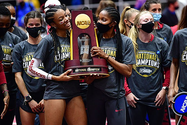 Arkansas runners Paris Peoples (left) and Daszay Freeman hold the NCAA indoor championship trophy Saturday, March 13, 2021, in Fayetteville.