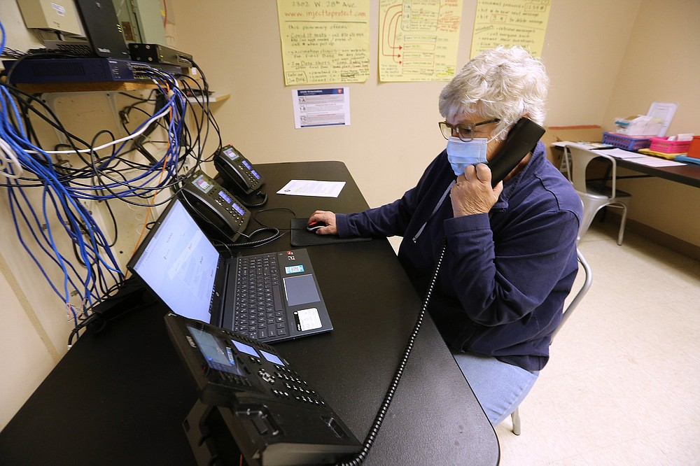 Leslie Trammell takes a phone call while setting up vaccine appointments Thursday at Doctor's Orders Pharmacy in Pine Bluff. Pharmacy owner Lelan Stice has been busy organizing supplies and remote vaccination clinics. (Arkansas Democrat-Gazette/Thomas Metthe)