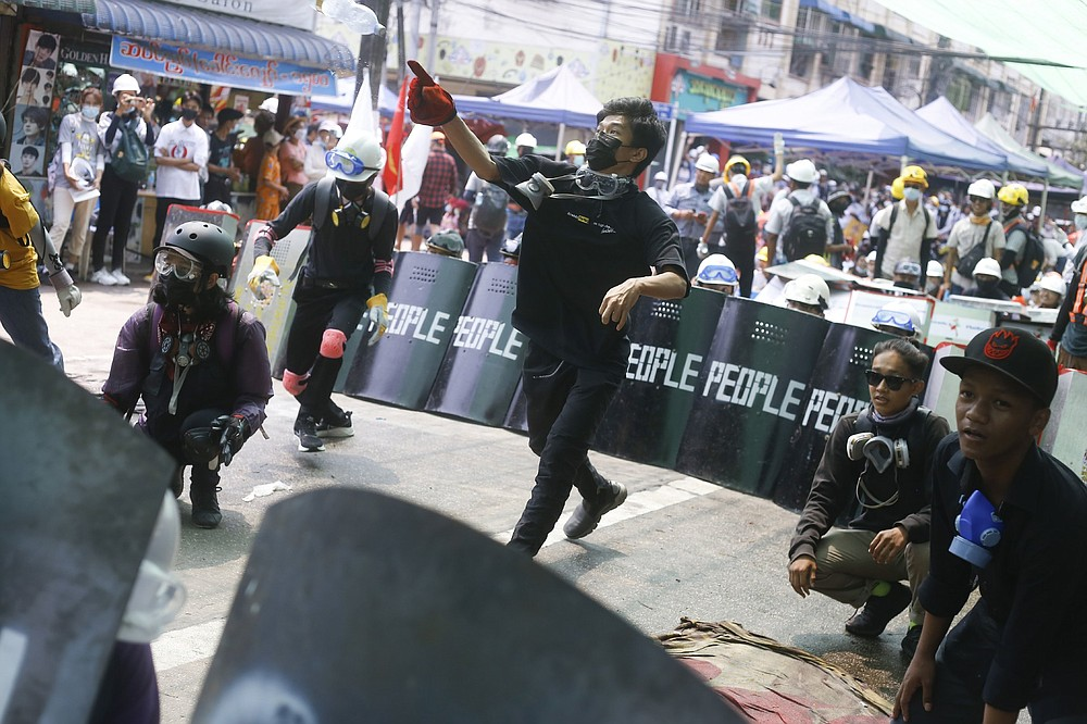 Anti-coup protesters in Rangoon practice a defensive formation Saturday using makeshift shields. (AP)