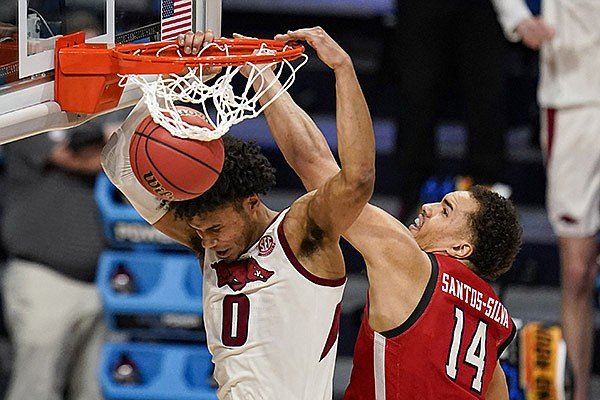 Arkansas forward Justin Smith (0) gets a dunk in front of Texas Tech forward Marcus Santos-Silva (14) in the second half of a second-round game in the NCAA men's college basketball tournament at Hinkle Fieldhouse in Indianapolis, Sunday, March 21, 2021. (AP Photo/Michael Conroy)