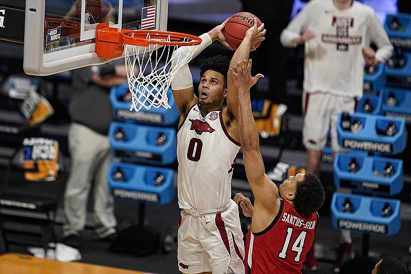 Arkansas forward Justin Smith (0) gets a dunk in front of Texas Tech forward Marcus Santos-Silva (14) in the second half of Sunday's game at Hinkle Fieldhouse in Indianapolis. (AP Photo/Michael Conroy)
