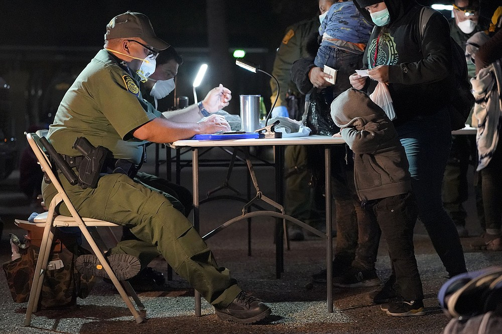 A U.S. Customs and Border Protection officer processes migrants who just crossed over from Mexico early Wednesday in Roma, Texas. Calls are growing for the Biden administration to offer more transparency on the border situation as it struggles to house and quickly process unaccompanied migrant children. (AP/Julio Cortez)