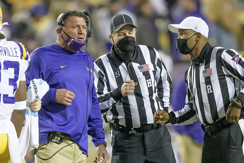 LSU head coach Ed Orgeron, left, questions a call during the first half of an NCAA college football game against Alabama in Baton Rouge, La., Saturday, Dec. 5, 2020. (AP Photo/Matthew Hinton)