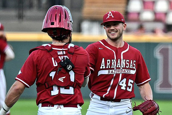 Arkansas pitcher Kevin Kopps (45) celebrates with catcher Casey Opitz following the final out of the Razorbacks' 11-5 victory over Mississippi State on Saturday, March 27, 2021, in Starkville, Miss. (Courtesy photo via Aaron Fitt/D1Baseball.com)