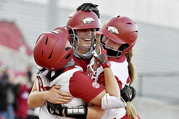 Arkansas batter Linnie Malkin (center) celebrates with teammates Aly Manzo (left) and Hannah McEwen (right) after hitting a two run home run against Mississippi State during an NCAA softball game on Friday, March 26, 2021, in Fayetteville. (AP Photo/Michael Woods)