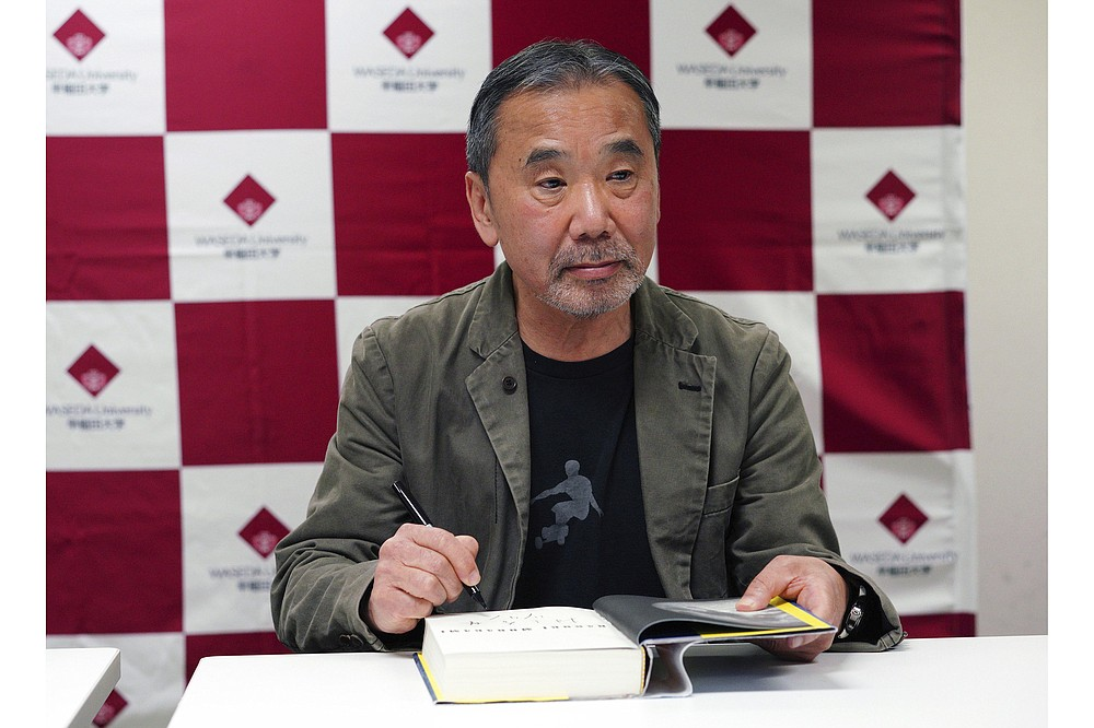 """In this 2018 file photo, Japanese novelist Haruki Murakami signs his name on his novel """"Killing Commendatore"""" during a news conference at Waseda University in Tokyo. (AP Photo/Eugene Hoshiko)"""