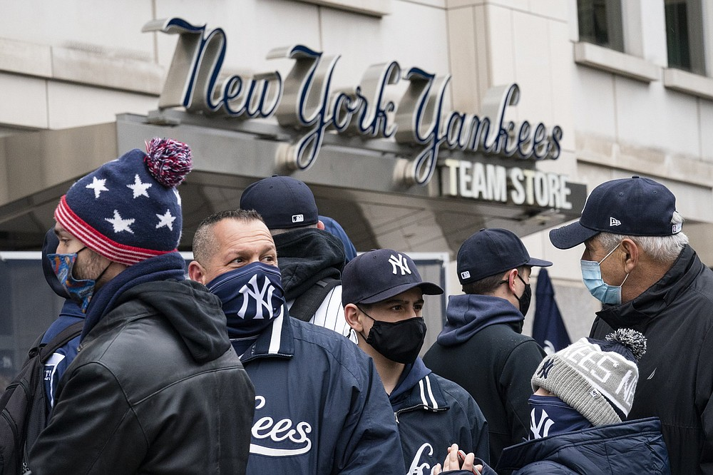 Spectators wait on a security line while wearing protective masks outside Yankee Stadium in New York before Thursday's Opening Day game against the Toronto Blue Jays. Major league teams will allow limited capacities this season except Texas, which is allowed to fill 100% of Globe Life Field.