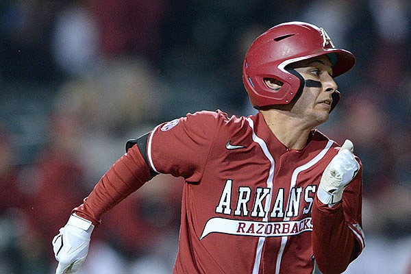 Arkansas second baseman Robert Moore heads to first after hitting a go-ahead RBI single during the seventh inning Friday against Auburn at Baum-Walker Stadium in Fayetteville. Arkansas scored five runs in the seventh to erase a 4-0 deficit en route to a 6-5 victory. More photos at arkansasonline.com/43auua/ (NWA Democrat-Gazette/Andy Shupe)