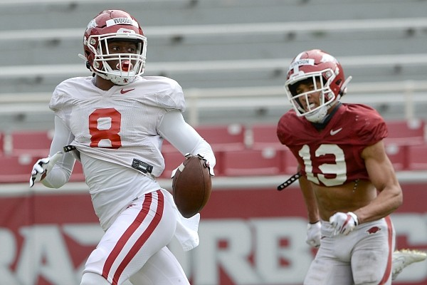 Arkansas receiver Mike Woods (8) makes a catch Saturday, April 3, 2021, ahead of defensive back Khari Johnson during a scrimmage at Razorback Stadium in Fayetteville. Visit nwaonline.com/210404Daily/ for the photo gallery.