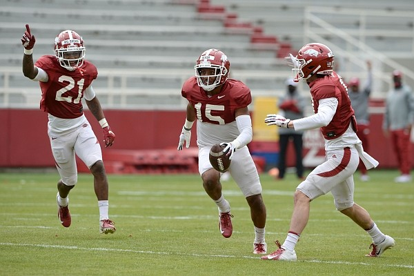 Arkansas defensive back Simeon Blair (15) celebrates an interception Saturday, April 3, 2021, with Montaric Brown (21) and Hudson Clark (right) during a scrimmage at Razorback Stadium in Fayetteville. Visit nwaonline.com/210404Daily/ for the photo gallery.