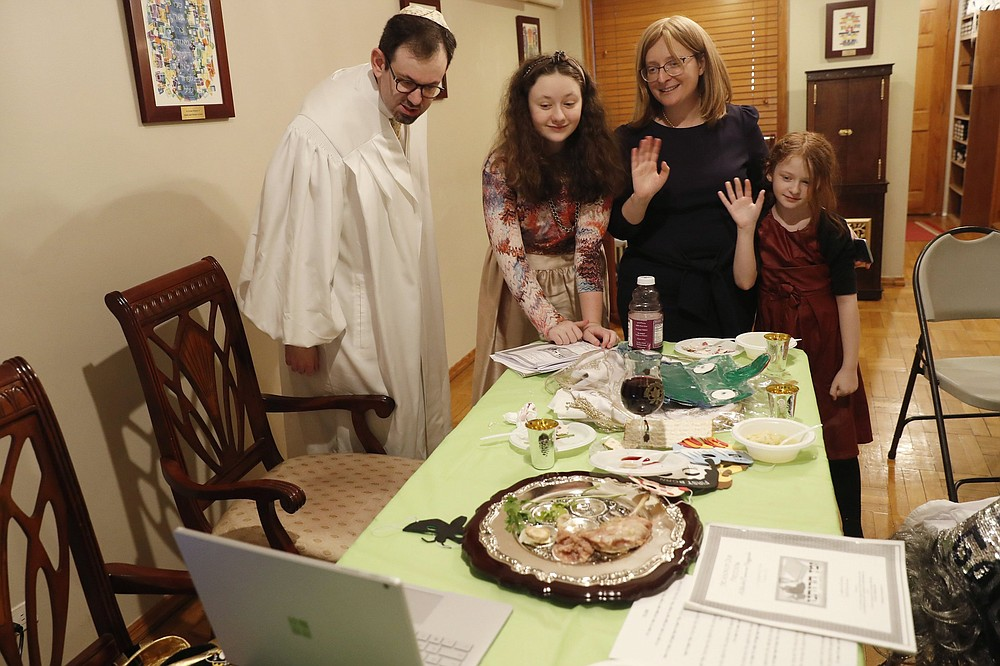 Rabbi Shlomo Segal (left) and his family wave goodbye to participants after he conducted a virtual Passover Seder for members of his congregation, friends and family broadcast on YouTube from his home in the Sheepshead Bay neighborhood of Brooklyn during the coronavirus outbreak in New York last April. From left are Segal; daughter Shira, 12; wife, Adina, and daughter, Rayna, 8. This year, the Sabbath led directly into Passover, limiting the use of technology for Segal and his congregants. Instead of streaming their Seder, the synagogue provided online workshops before Passover so families could do it on their own. Segal says that many of his members are still reluctant to gather together in person.