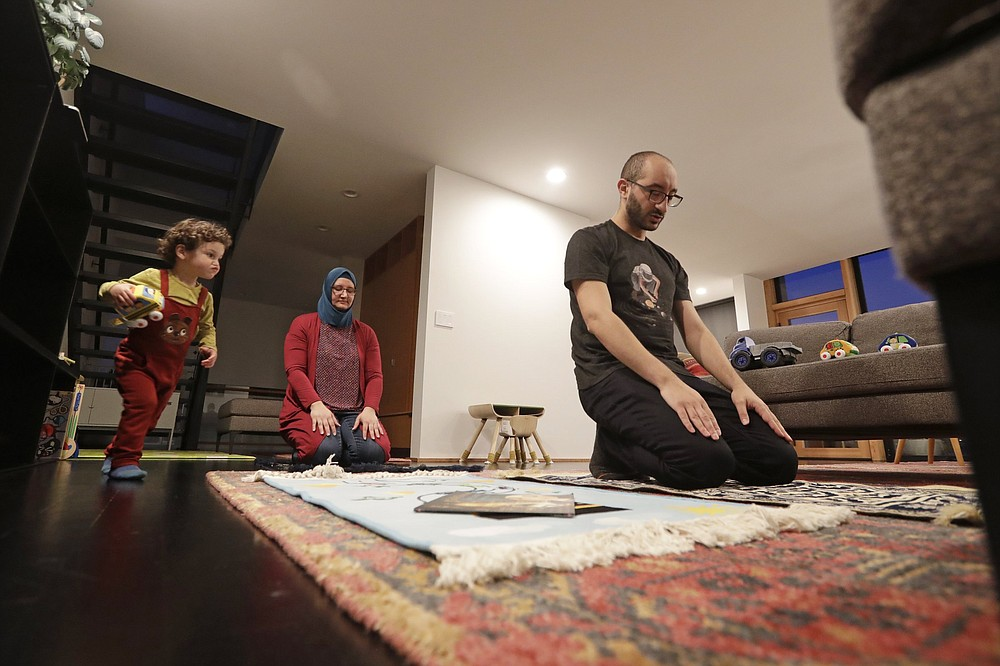 Ahmad Kamel (right) performs the Maghrib prayer with his wife, Nadia Chaouch, as their son Ahmad Kamel runs past after the family broke the Ramadan daily fast just after sunset in their home last April during the coronavirus outbreak in Seattle.