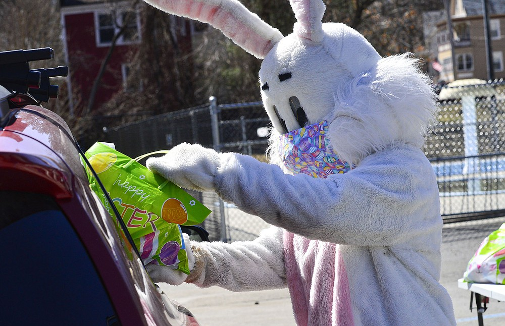 A masked Easter Bunny hands out baskets to children in a drive-thru event Saturday at the Rockingham Recreation Center in Bellows Falls, Vt.