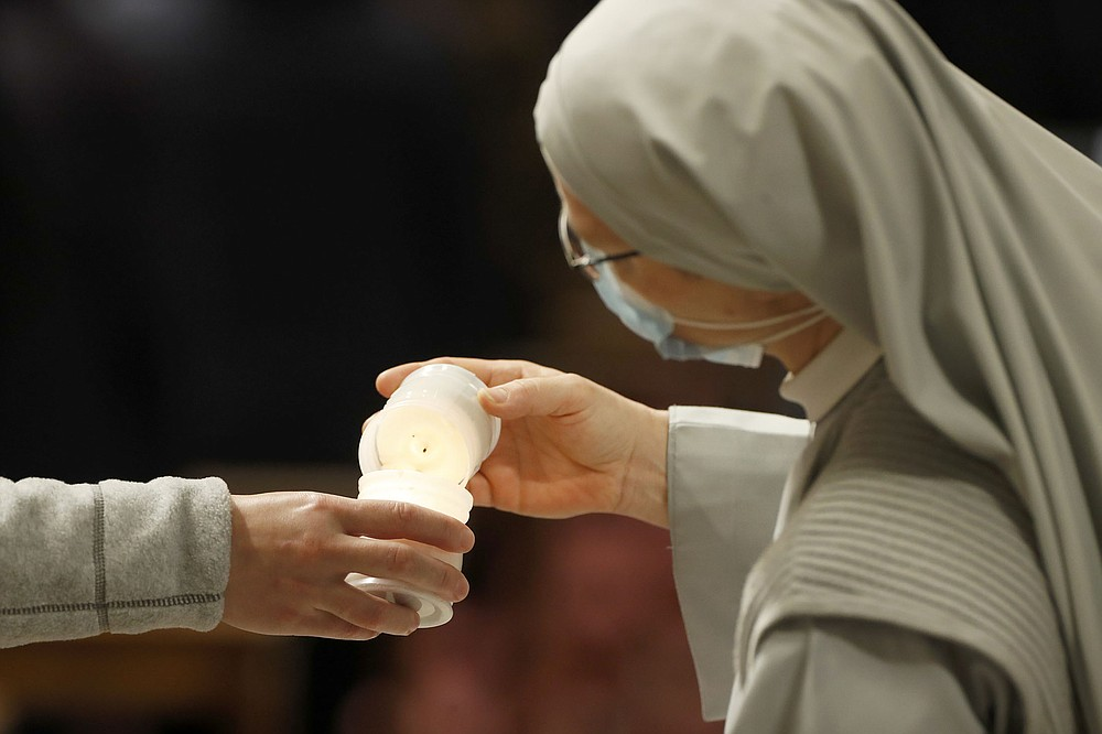 Worshippers light candles Saturday during the Easter Vigil at St. Peter's Basilica at the Vatican. Usually a long, late-night ritual, this year's vigil service started earlier than usual to respect Italy's curfew.
