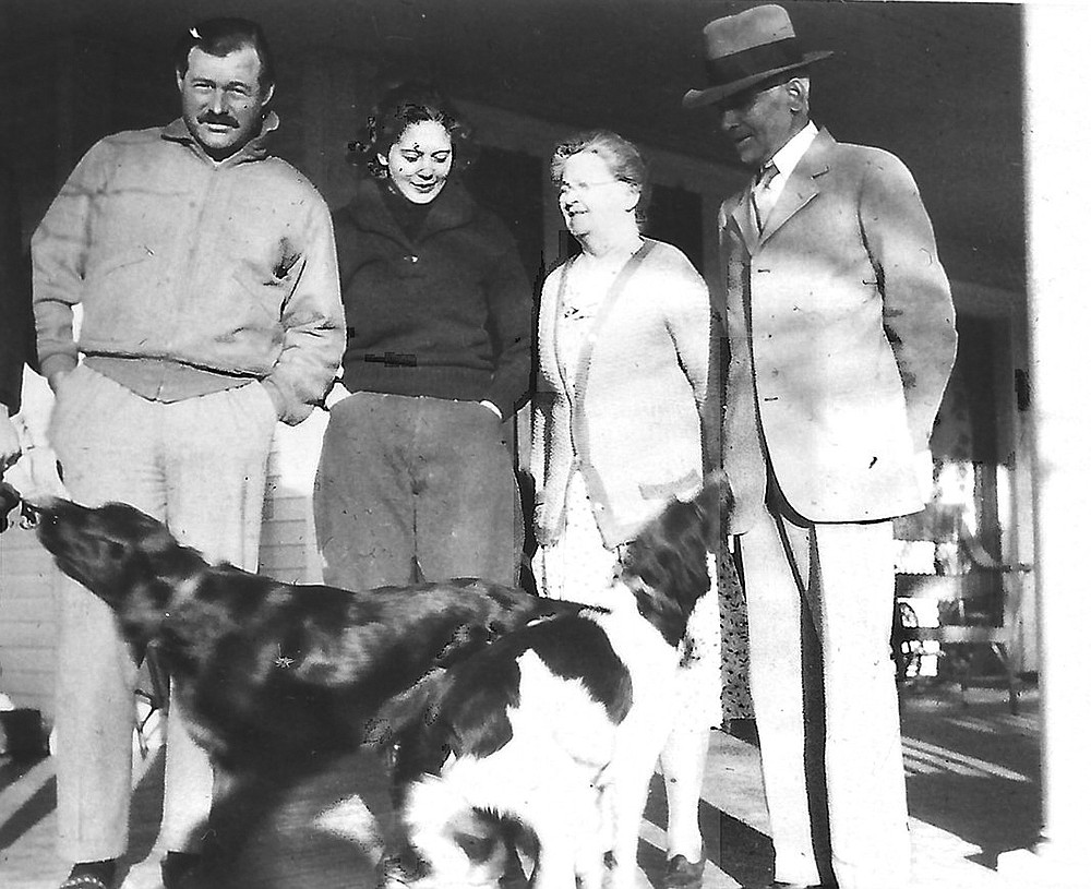 Ernest Hemingway stands on the front porch of his in-laws' home in Piggott in 1932 with Pfeiffer cousin Barbara Peck (second from left) and Paul and Mary Pfeiffer, parents of Pauline Pfeiffer. Around Piggott, the famous writer was best-known to the locals as Paul Pfeiffer's son-in-law. (Special to the Democrat-Gazette)