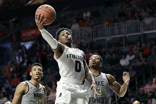 Miami guard Chris Lykes (0) goes up for a shot against Wake Forest forward Ody Oguama (33) and guard Andrien White (13) during the first half of an NCAA college basketball game in Coral Gables, Fla., on Saturday, Feb. 15, 2020. (AP Photo/Wilfredo Lee)