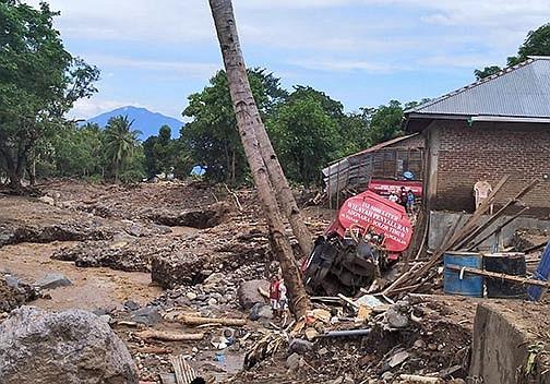People survey the damage Wednesday at a flooding-struck village in Waewerang on Adonara Island, East Nusa Tenggara province, Indonesia. (AP/Rofinus Monteiro)
