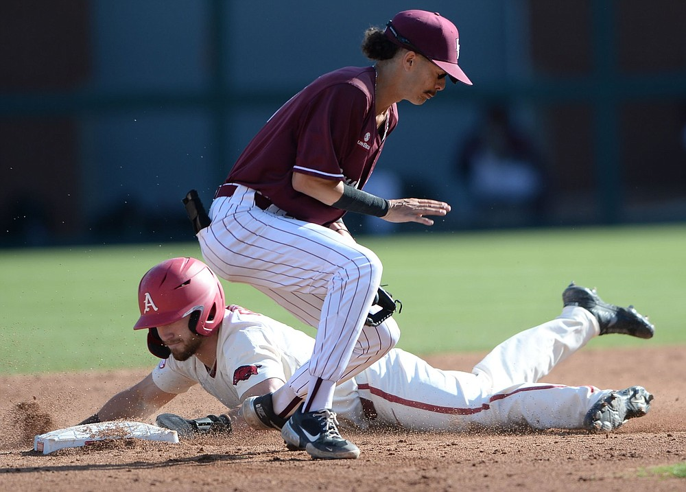 Arkansas' Zack Gregory slides safely into second base behind UALR's Jorden Hussein during Wednesday's game in Fayetteville.
