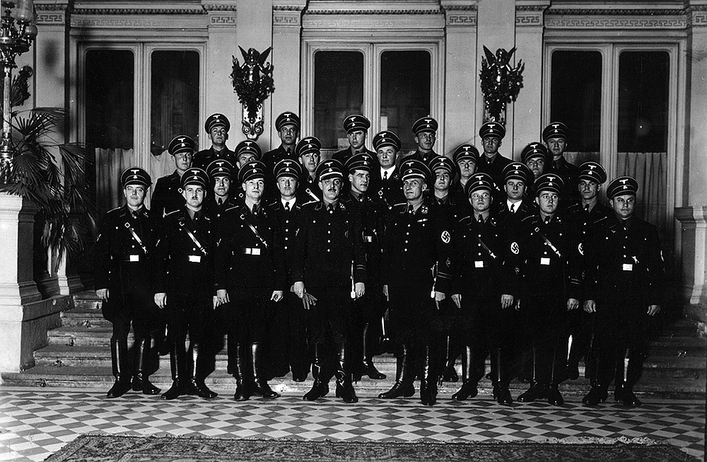 """In an undated photo provided by the National Archives of Slovenia, Franz Josef Huber (front row center holding gloves) poses with his Vienna Gestapo team. Huber gave orders """"to arrest immediately undesirable, particularly criminally motivated Jews and transfer them to the concentration camp Dachau."""" (The New York Times/National Archives of Slovenia)"""