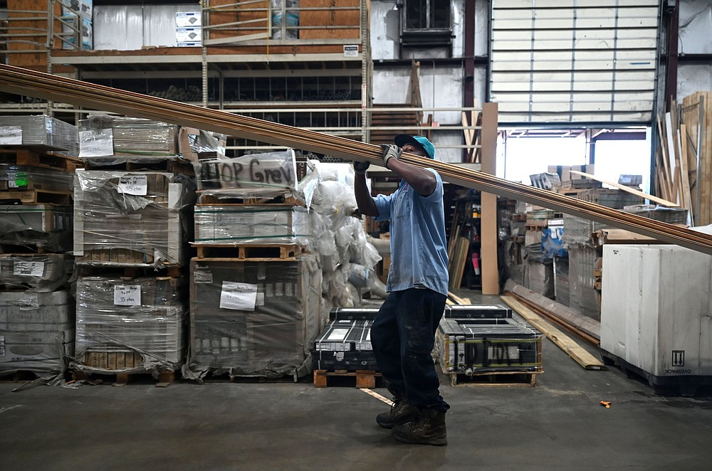 Khiry Smith carries a load of lumber through the warehouse during his shift at Lumber One in Mayfl ower on Tuesday. See more photos at arkansasonline.com/411lumber/. (Arkansas Democrat-Gazette/Stephen Swofford)