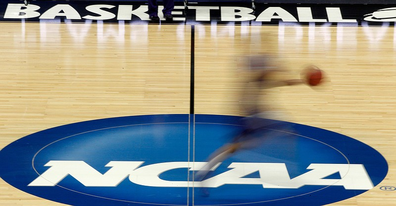FILE - In this March 14, 2012, file photo, a player runs across the NCAA logo during practice in Pittsburgh before an NCAA tournament college basketball game.