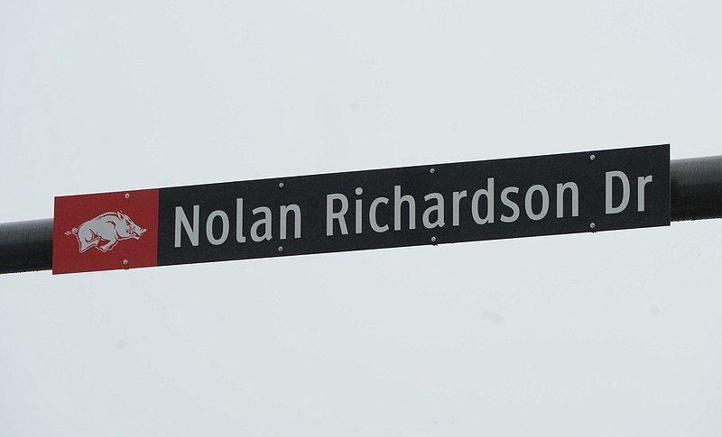 A sign marking Nolan Richardson Drive hangs Friday, April 16. 2021, on a utility pole over Razorback Road following an unveiling ceremony for the newly renamed street on the University of Arkansas campus in Fayetteville. The Fayetteville City Council voted last month to rename what was known as Leroy Pond Drive to Nolan Richardson Drive, in honor of the national championship-winning former head menÕs basketball coach of the Arkansas Razorbacks. In turn, what was known as Government Avenue leading to Fayetteville National Cemetery will be renamed Lt. Col. Leroy Pond Avenue, in honor of the World War II veteran awarded with the Purple Heart, Silver Star and other awards, who was wounded in Germany and died in 1945.