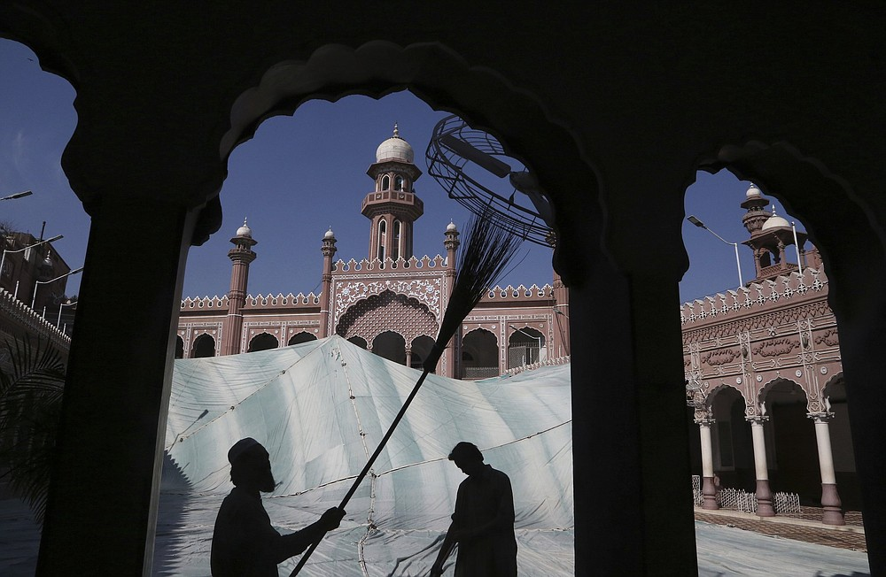 Volunteers clean the outer areas of the historic Mohabat Khan Mosque ahead of the Muslim fasting month of Ramadan, in Peshawar, Pakistan. Muslims are in the midst of their second Ramadan, which began Monday in the midst of the covid-19 pandemic. (AP/Muhammad Sajjad)