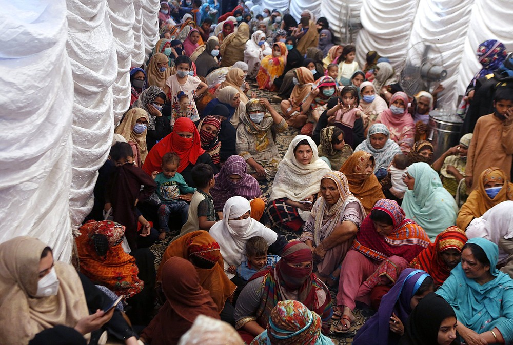 Women wait to receive food assistance for the Muslim fasting month of Ramadan, in Lahore, Pakistan on April 10. Muslims are facing their second Ramadan in the shadow of the pandemic. (AP/K.M. Chaudary)