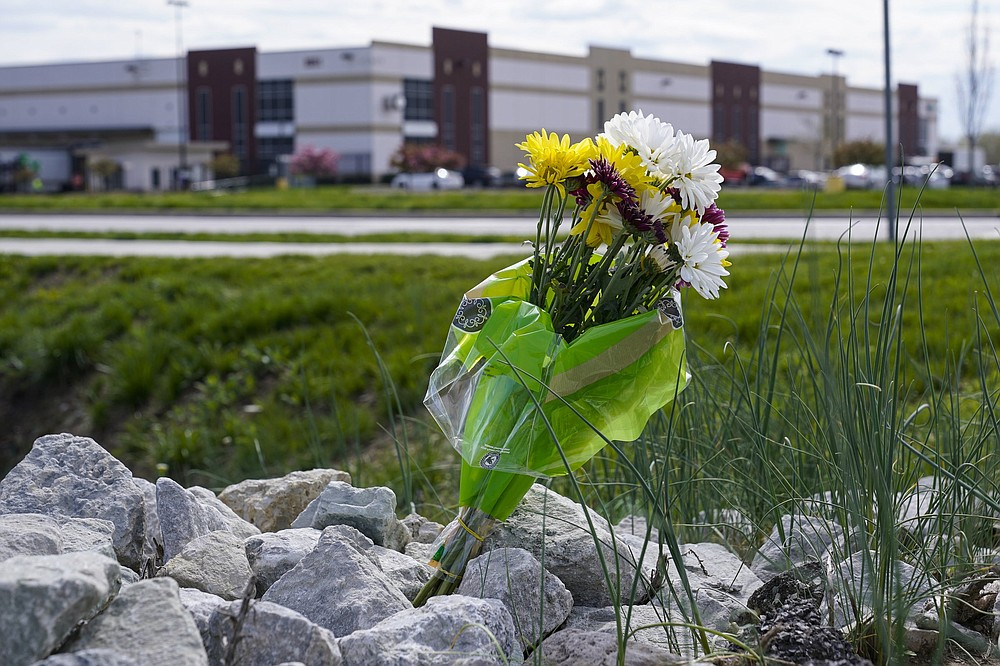 A single bouquet of flower sits in the rocks across the street from the FedEx facility in Indianapolis on April 17 where eight people were shot and killed the day before in the latest in a spate of mass shootings in the United States after a relative lull during the pandemic.