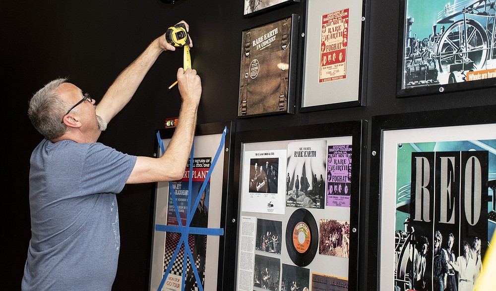 """Rick Hall measures a space to hang an item in the exhibit """"Play It Loud: Concerts at Barton Coliseum,"""" which opens today at the Old Statehouse Museum. (Arkansas Democrat-Gazette/Cary Jenkins)"""